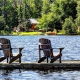 Deck chairs on a dock overlooking a lake with a cabin on the shore.