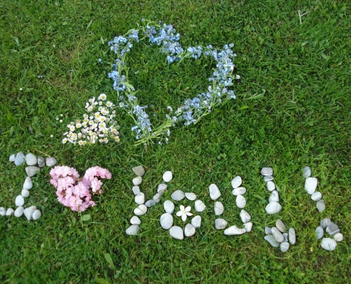 "Love your lawn. Lawn with ""I Love You"" written in flowers and stones."